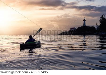 Adventurous Woman Is Sea Kayaking Near A Lighthouse During Winter. Dramatic Colorful Sunset Artistic