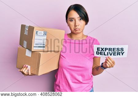 Beautiful young woman with short hair holding delivery box with express delivery text depressed and worry for distress, crying angry and afraid. sad expression.
