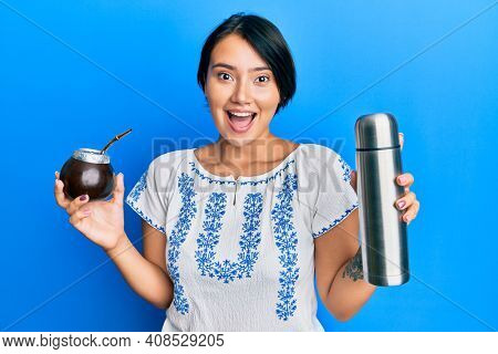 Beautiful young woman with short hair drinking mate infusion celebrating crazy and amazed for success with open eyes screaming excited.