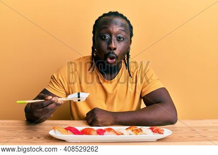 Handsome young black man eating sushi sitting on the table scared and amazed with open mouth for surprise, disbelief face