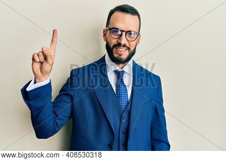 Young man with beard wearing business suit and tie showing and pointing up with finger number one while smiling confident and happy.