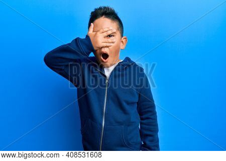 Little boy hispanic kid wearing casual sporty jacket peeking in shock covering face and eyes with hand, looking through fingers afraid