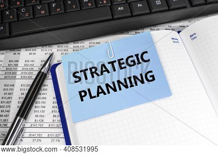 Strategic Planning Is Written On A Blue Note Sheet That Is Located On A Notepad. Financial Document