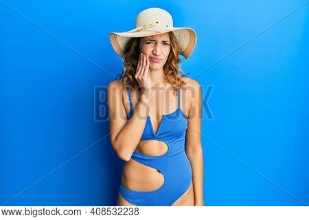 Young caucasian woman wearing bikini and summer hat touching mouth with hand with painful expression because of toothache or dental illness on teeth. dentist
