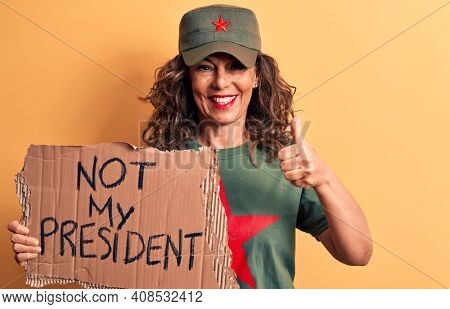 Middle age brunette communist woman holding banner with not my president message smiling happy and positive, thumb up doing excellent and approval sign