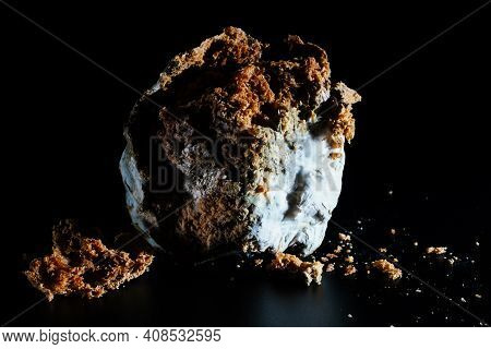 Spoiled Bread With Mold Isolated On A Black Background, Close-up. Violation Of Food Storage Conditio