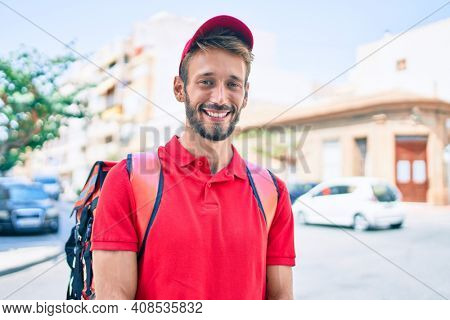 Caucasian delivery man wearing red uniform and delivery backpack smilly happy outdoors