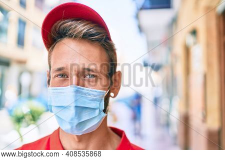 Caucasian delivery man wearing red uniform and coronavirus safety mask