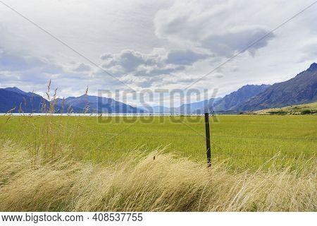 Rural Landscape Between Converging Mountain Ranges In Central Otago New Zealand.
