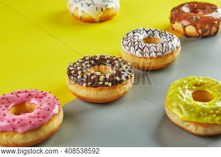 Multicolored Donuts With Glaze And Sprinkles On A Yellow-gray Background