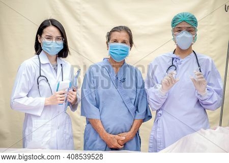 2 Female Doctors And Senior Patient Standing At The Field Hospital And Wore Masks Due To The Covid 1