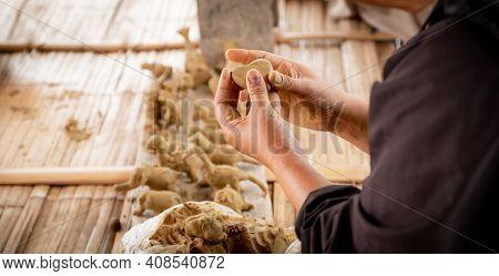 A Woman's Hand Sculpt A Heart-shaped Clay.