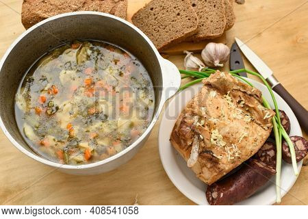 baked meat, soup and blood sausage on a plate, green onion and garlic on wooden background, home cooking