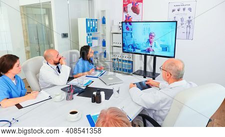 Team Of Medical Staff During Video Conference With Doctor In Hospital Meeting Room. Medicine Staff U