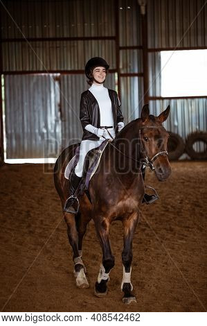 Young Woman Is Engaged In Equestrian Sports, Training On Horseback