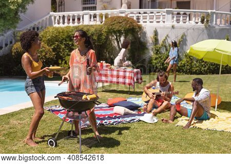 Diverse group of friends having barbecue and talking at a pool party. Hanging out and relaxing outdoors in summer.