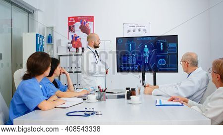 Man Doctor Presenting Human Internal Structure In Front Of Attantive Colleagues Using Digital Monito