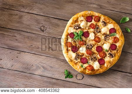 Supreme Pizza With Pepperoni, Mushrooms And Mozzarella Cheese On Wooden Table, Top View, Copy Space.