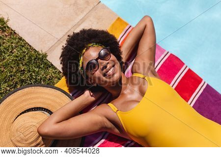 Mixed race woman sunbathing by pool on a sunny day smiling. Hanging out and relaxing outdoors in summer.