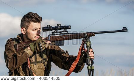 Hunter With Hunting Gun And Hunting Form To Hunt. Hunter Is Aiming. Shooter Sighting In The Target.