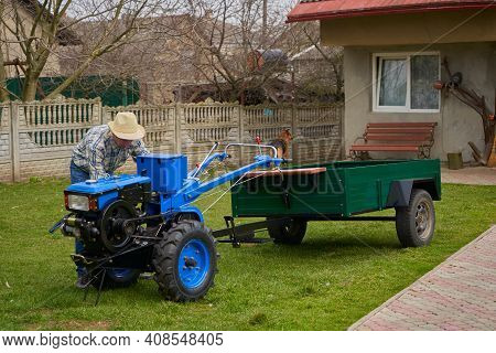 Start The Tractor Engine, Farmer In Hat Starting Engine With Hands Spinning Engine Flywheel