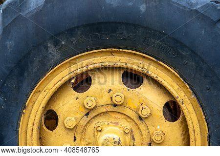 Heavy Machinery Wheel Closeup. Rustic Machine Tire. Tractor Or Grader Detail. Heavy Machinery Wheel