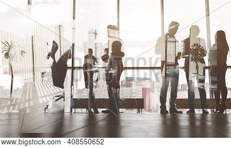 Silhouettes Of People Against The Window. A Team Of Young Businessman Working And Communicating Toge