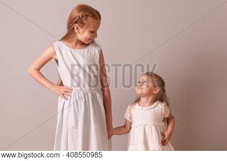 Sisters Look At Each Other. Girls Hold Hands