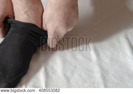 An Adult Man's Hands Put On New Socks. A Man At Home In The Morning Puts Gray Socks On His Leg. Clou