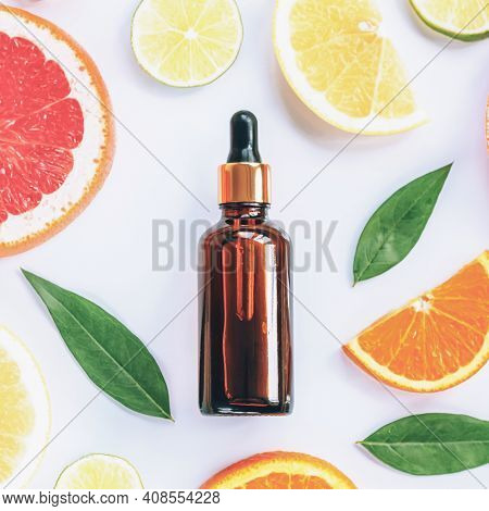 Glass Bottle With Cosmetic Serum And Sliced Citrus Fruits On White Background. Natural Cosmetics Wit