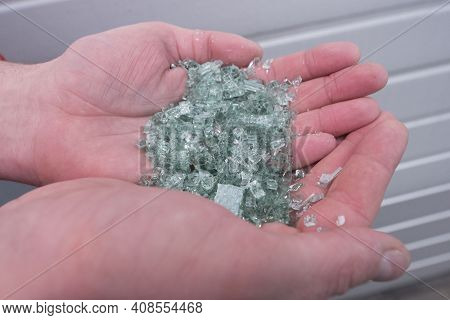 Person Holding Glass Splinters In Their Hands
