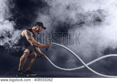 Bearded Athletic Looking Bodybulder Work Out With Battle Rope On Dark Studio Background With Smoke.