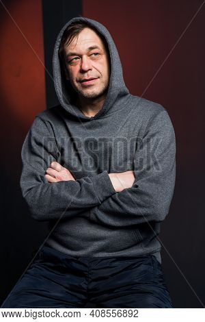 Studio Portrait Of A 40-50-year-old Laughing Man In A Gray Hoodie On A Neutral Background With A Hoo