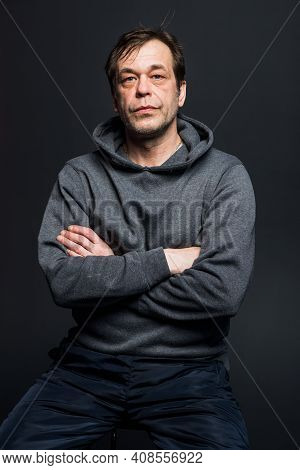 Studio Portrait Of A 40-50-year-old Serious Man In A Gray Hoodie On A Neutral Background, Looking Di