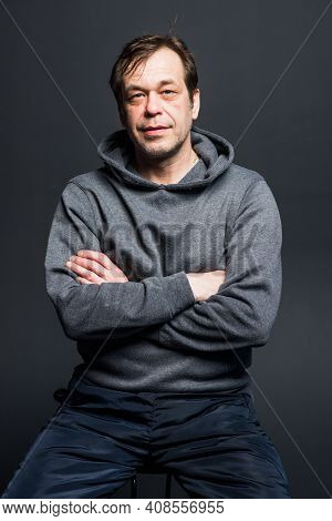 Studio Portrait Of A 40-50-year-old Smiling Man In A Gray Hoodie On A Neutral Background, Looking Di
