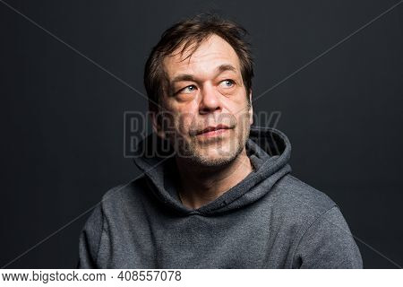 Studio Portrait Of A 40-50-year-old Man In A Gray Hoodie On A Neutral Background, Close-up, Eyes Dir