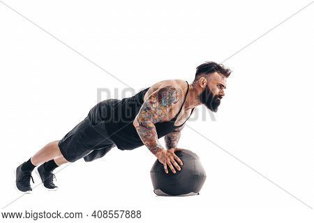 Muscular Tattooed Bearded Male Exercising Fitness Weights Medicine Ball Push Ups Exercises In Studio