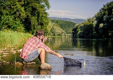 Hipster Fishing With Spoon-bait. Successful Fisherman In Lake Water. Fly Fish Hobby Of Man. Hipster