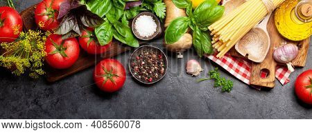 Italian cuisine ingredients. Garden tomatoes, pasta, herbs and spices. Top view flat lay