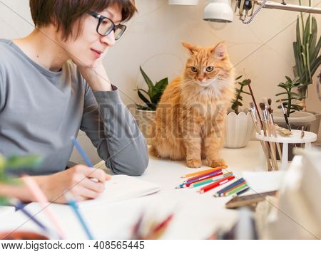 Woman With Short Hair Cut Is Drawing In Notebook. Cute Ginger Cat Sits Near Her. Fluffy Pet And Arti