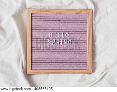 Top View On Pink Letter Board With Season Greeting Hello Spring. Crumpled White Textile Background.