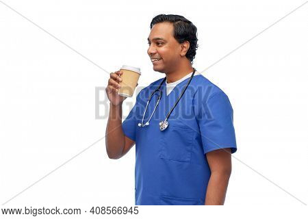 healthcare, profession and medicine concept - happy smiling indian doctor or male nurse in blue uniform with takeaway coffee cup and stethoscope over white background