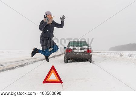 Enraged Young Woman Is Talking On A Mobile Phone, Jumping In Anger Near A Warning Road Sign-a Triang