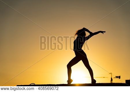 Female Dancer On The Edge Of Rooftop Dancing Go-go On The Orange Sky Background. Concept Of Joy And