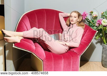 Handsome glamorous girl is posing  on armchair in her cozy home. Home interior, furniture. Lifestyle.