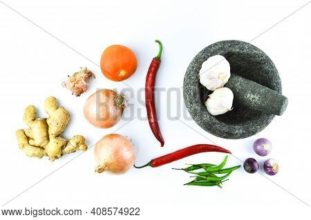 Top View Of Pestle And Mortar With The Onions, Garlic, Red Chilies, Green Chilies, Ginger And Tomato