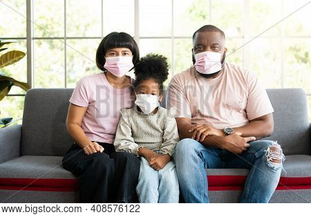 Mixed Race Family Sitting On The Sofa And Wearing Medical Face Masks For Against Coronavirus World P
