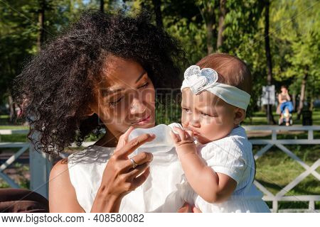 Black Woman Gives Water To Her Child Using Baby Bottle In Summer Park. Little Toddler Girl Drinks Wa