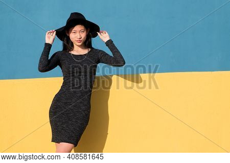 Fashionable Asian Young Woman Posing In A Black Tight Dress And Hat On A Colorful Yellow And Blue Ba