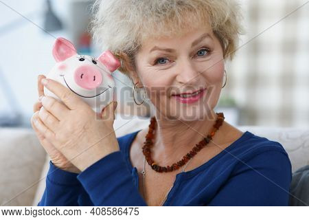 Portrait Of An Elderly Woman Who Holds Piggy Bank In Her Hand. Pension Fund And Deductions Concept